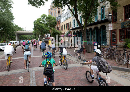 Bicyclists in the Tour de Fat parade ride down St Anthony Main. Minneapolis Minnesota MN USA - Stock Photo