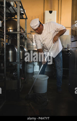 Male baker cleaning floor with floor mop - Stock Photo