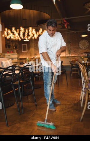 Male baker cleaning floor with floor mop - Stock Photo
