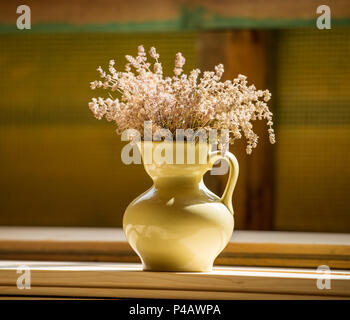 pitcher with wildflowers is standing on a wooden table in the room. Rural motive. - Stock Photo