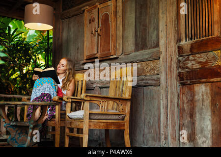 Attractive girl sit on open-air veranda of wooden bungalow with tropical garden view, read romance in paper book. Young woman relaxing in luxury villa - Stock Photo