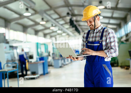 Technician working in factory and doing quality control - Stock Photo