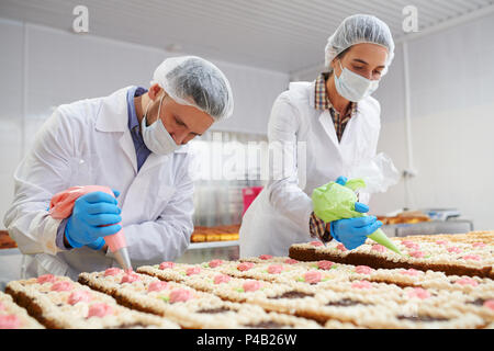 Process of cakes decorating on factory - Stock Photo