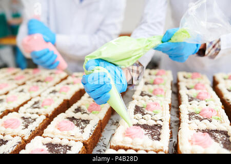Cakes decorating in confectionery factory - Stock Photo
