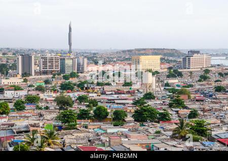High angle view over slums of Luanda with Mausoleum of Agostinho Neto tower in background, Angola, Africa. Antonio Agostinho Neto served as the 1st Pr - Stock Photo