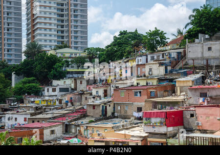 Colorful houses of the poor inhabitants of Luanda, Angola. These ghettos resemble Brasilian favelas. In the background the high rise buildings of the  - Stock Photo