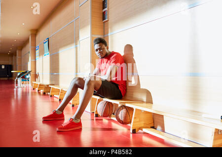 Black basketball player resting on bench - Stock Photo