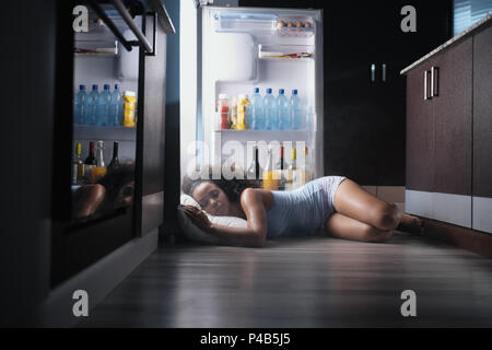 Young hispanic woman suffering for summer heat and lack of air conditioning at home. Black girl covered with sweat sleeping on floor with head inside  - Stock Photo