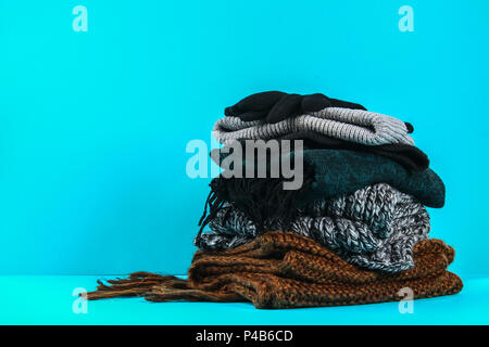 Winter and autumn clothes, hats, scarves, gloves on a blue pastel background - Stock Photo