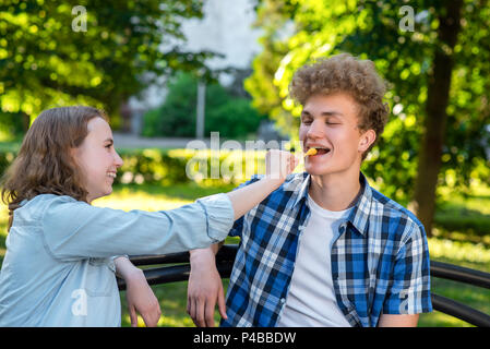 Young couple in love. Summer in park sit on a bench. A girl is feeding a guy with food. The guy smiles happily. The concept of a happy relationship. - Stock Photo