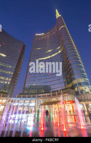 View of the Unicredit Tower from the fountains in Gae Aulenti square during the evening. Milan, Lombardy, Italy. - Stock Photo
