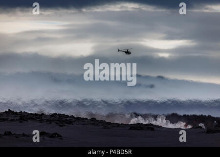 Helicopter flying over the volcano eruption at the Holuhruan Fissure, near the Bardarbunga Volcano, Iceland. August 29, 2014 a fissure eruption started in Holuhraun at the northern end of a magma intrusion, which had moved progressively north, from the Bardarbunga volcano. - Stock Photo