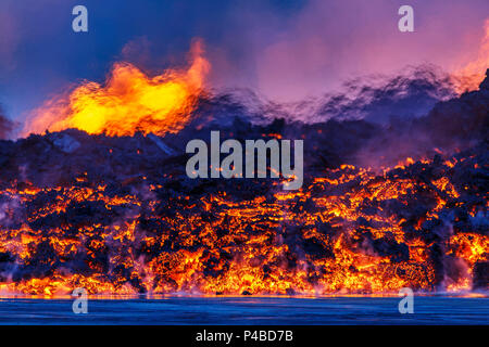 Glowing lava from the eruption at the Holuhraun Fissure, near the Bardarbunga Volcano, Iceland. A close-up night view of the lava flow. Heat from the lava distorts the view of the fountains in the distance. August 29, 2014, a fissure eruption started in Holuhraun at the northern end of a magma intrusion that had moved progressively north, from the Bardarbunga volcano. Bardarbunga is a stratovolcano located under Vatnajokull, Icelands most extensive glacier. Picture date- Sept 2, 2014 - Stock Photo