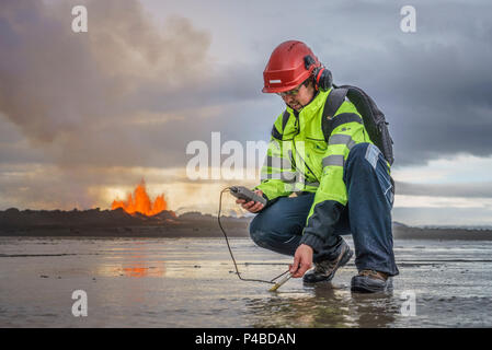 Scientist taking measurements by the eruption site at Holuhraun, near Bardabunga Volcano, Iceland. August 29, 2014 a fissure eruption started in Holuhraun at the northern end of a magma intrusion, which had moved progressively north, from the Bardarbunga volcano. Bardarbunga is a stratovolcano located under Vatnajokull, Iceland's most extensive glacier. Picture Date-Sept. 2, 2014 - Stock Photo
