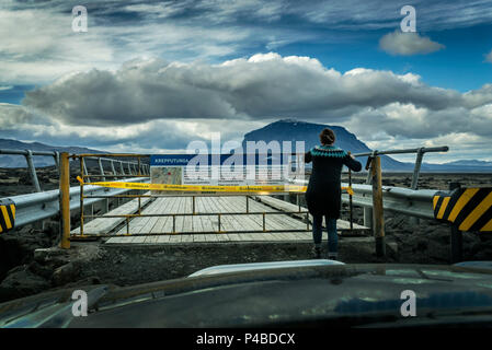 Woman standing by a closed bridge-Krepputunga area, by the Holuhraun Fissure Eruption, near the Bardarbunga Volcano, Iceland. August 29, 2014 a fissure eruption started in Holuhraun at the northern end of a magma intrusion, which had moved progressively north, from the Bardarbunga volcano. Picture Date-Sept. 2, 2014 - Stock Photo