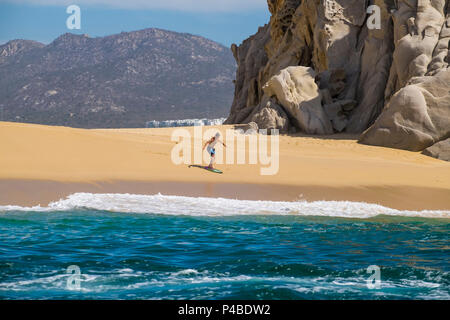 Surfer at Beach of love and divorce in Cabo San Lucas in the state of Baja California Sur in northern Mexico - Stock Photo