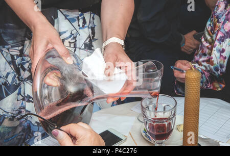 The sommelier pours wine into a glass from a bowl. Aeration of red wine. Decanter. - Stock Photo