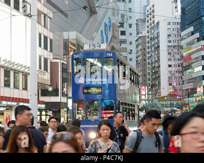 View of pedestrians crossing the road in front of a tram on Hennessy Road in Causeway Bay Hong Kong at night - Stock Photo