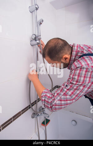 Handyman fixing the shower the bathroom - Stock Photo