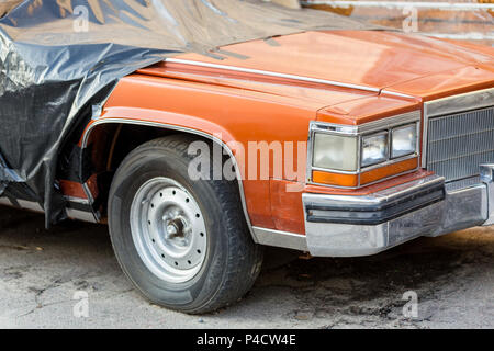 Old wrecked covered car at back yard of workshop. Abandoned convertible vehicle under black curtain near garage doors. Recycling and utilization. - Stock Photo