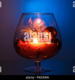 A burning candle in a glass vase, decoration and various Christmas elements on a dark blue background. - Stock Photo