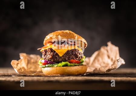 Close-up home made beef burger on wooden table. - Stock Photo