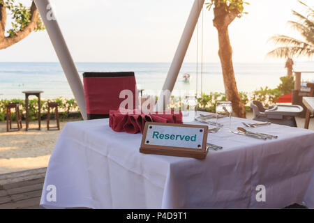 Reserved table dinner time in luxury restaurant on sea background. - Stock Photo
