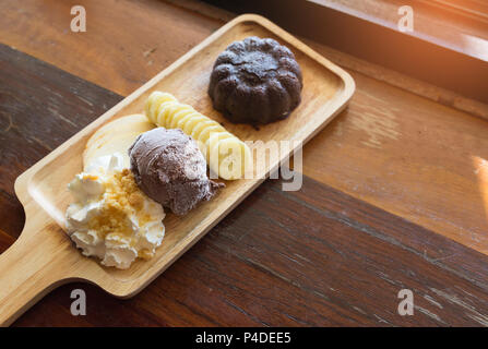 Chocolate lava cake set, with chocolate icecream banana apple fruit and whipped cream on wood table in the cafe, dessert summer. - Stock Photo