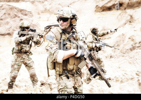 Special forces teamwork in desert raid operation - Stock Photo