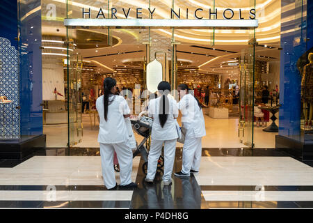 Female maids wait outside Harvey Nichols store in the Prestige mall inside The Avenues shopping mall in Kuwait City, Kuwait. - Stock Photo