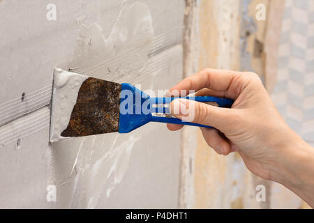 hand plastering wall with spatula during repair - Stock Photo