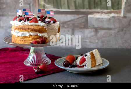 Patriotic angelfood cake with red white and blue berries and  American flags, and a slice ready to eat - Stock Photo