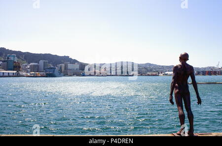 Wellington, New Zealand - 13 February  2016: Wellington Harbour on a summer day with Max Patte's iconic  'Solace in the Wind' statue in the foreground - Stock Photo