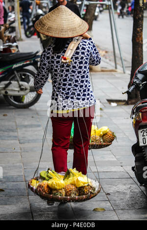 Hanoi, Vietnam - March 15, 2018: Lady selling cut pineapples on the street in Hanoi - Stock Photo
