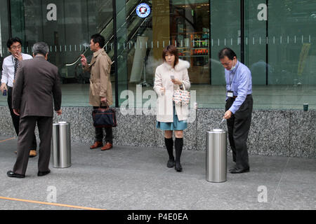 Japanese people smoke cigarettes in a special  smoking area on the street of Tokyo, Japan – jan, 24, 2011. - Stock Photo