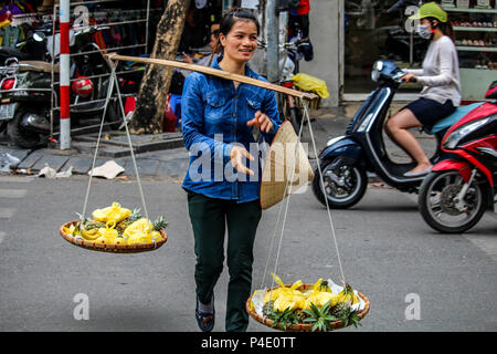 Hanoi, Vietnam - March 15, 2018: Girl selling fruits on the trafficked streets of Hanoi - Stock Photo