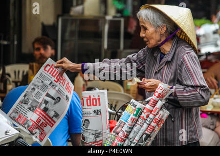 Hanoi, Vietnam - March 15, 2018: Senior lady selling local newspapers with a bicycle - Stock Photo
