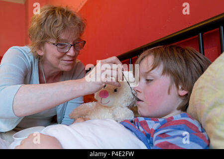 mother looking after her ill son in his bed - Stock Photo