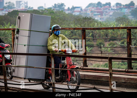 Hanoi, Vietnam - March 15, 2018: Vietnamese man transporting an enormous fridge on his motorbike - Stock Photo