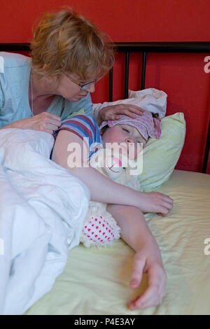 mother comforting her ill son in his bed - Stock Photo