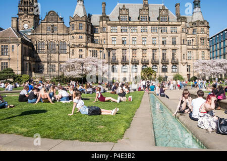 People relaxing and sitting on the grass at the Peace Gardens with the Town Hall in the background, Sheffield city centre, England, UK - Stock Photo