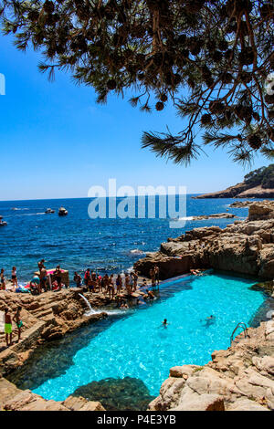 Girona, Spain - August 13, 2016: Tourists bathing in a blue natural salty water pool Es Cau south of the village of Begur in Costa Brava - Stock Photo