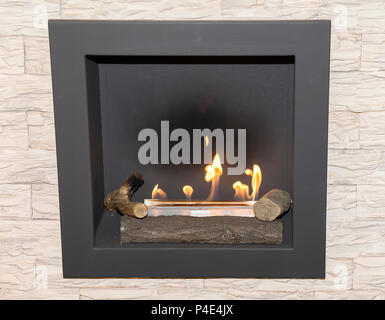 Artificial natural gas fireplace with a natural stone in the living room. - Stock Photo