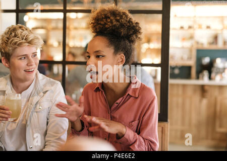 Young woman talking with friends over drinks in a cafe - Stock Photo