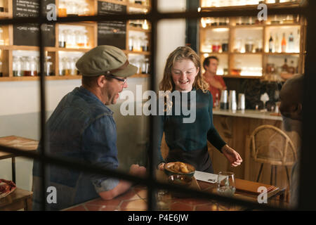 Smiling waitress serving food to a bistro customer - Stock Photo