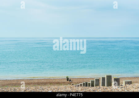 Pebble beach scene of calm sea on bright day. Wooden posts of varying heights lead towards the shoreline. - Stock Photo