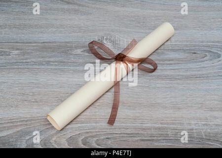 a diploma rolled up and tied with a red ribbon on the table with a pair of glasses - Stock Photo
