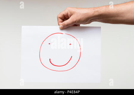 a sheet of paper with a drawing of a smiling face - Stock Photo