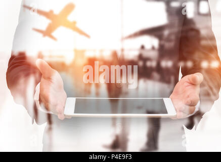 Double exposure businessman holding tablet on hand with blurred terminal airport background. Transportation and Travel airline concept. - Stock Photo