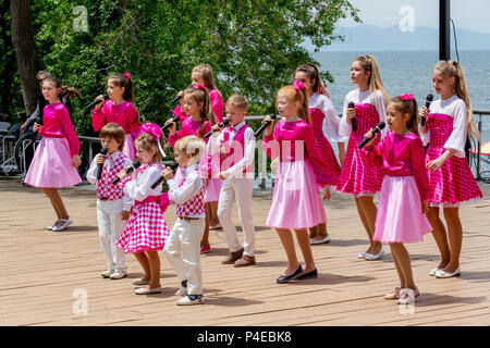 Russia, Vladivostok, 06/12/2018. Kids in colourful clothings perform song on stage. Celebration of annual Russia Day on June 12. Kids' performance. Ho - Stock Photo